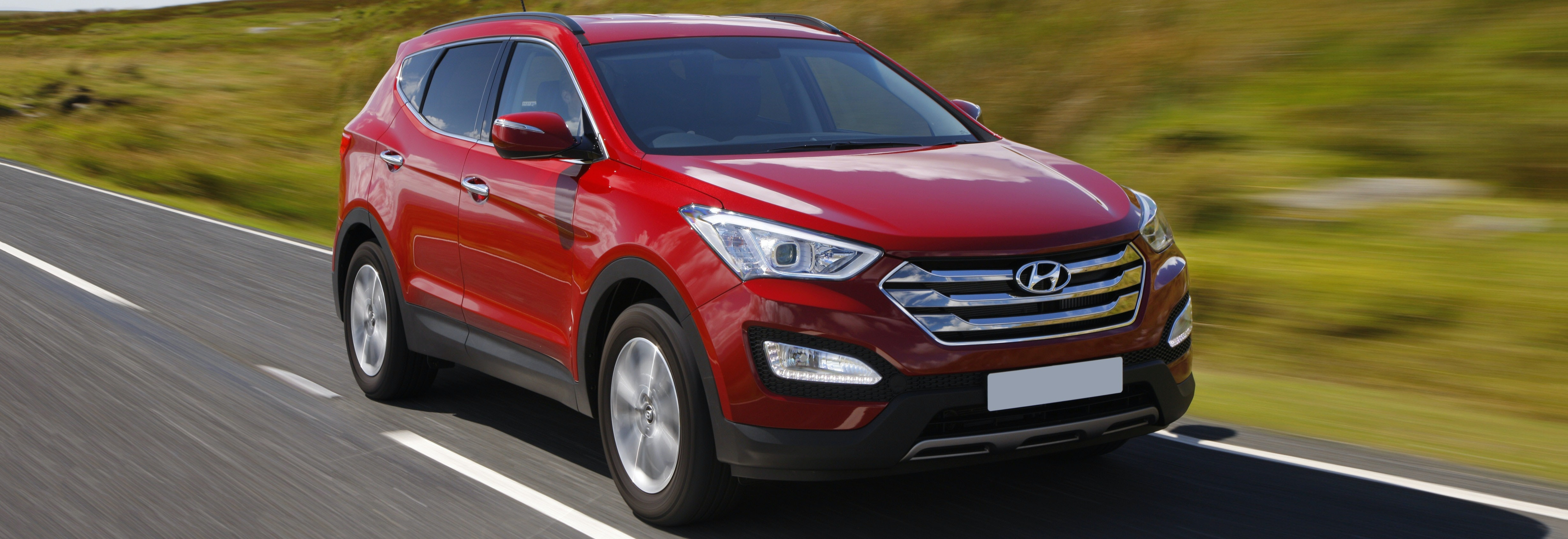 Red Hyundai Santa Fe driving, viewed from the front