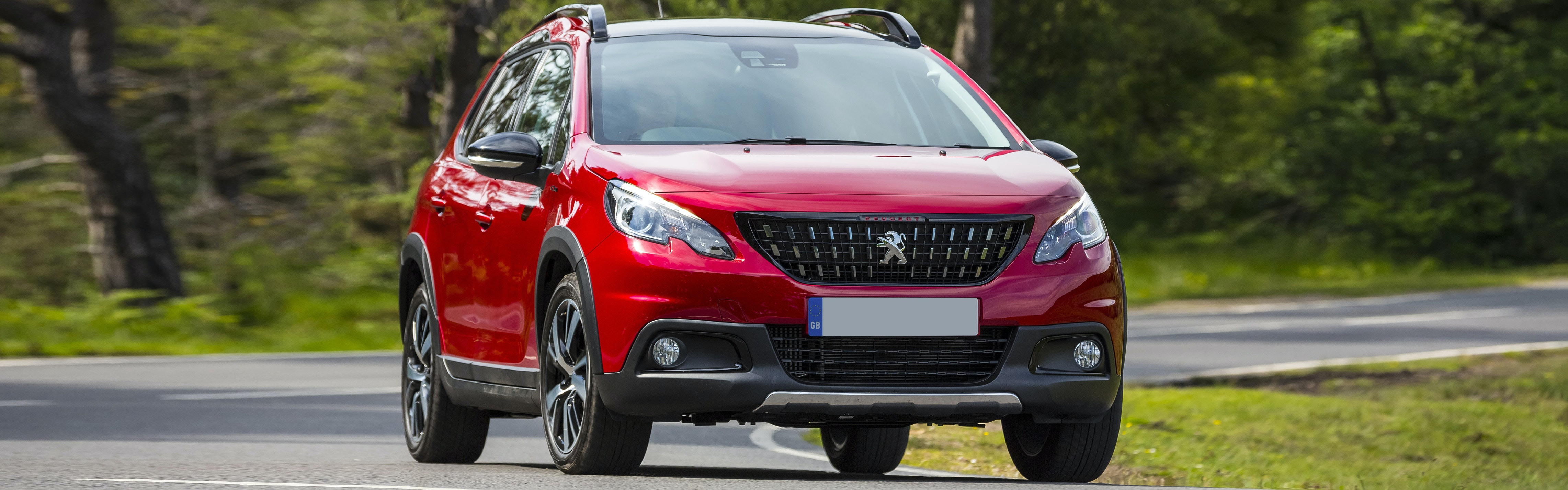 Red Peugeot 2008 driving, viewed from the front