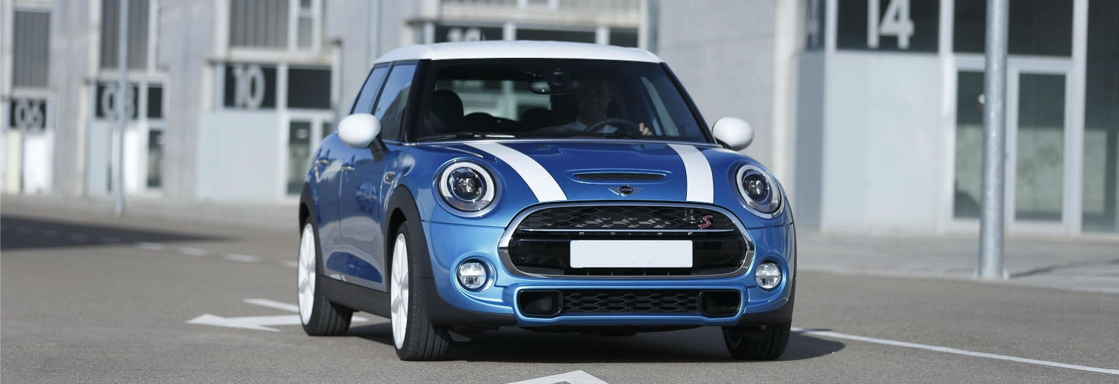 Blue Mini Hatchback with white stripes parked, viewed from the front